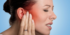 sick female having ear pain touching her painful head