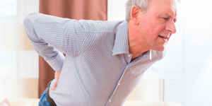 Senior having back pain at home