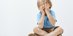 Indoor shot of cute european child with lovely haircut and vitiligo, covering face with palms while sitting, playing hide and seek with older brother, having fun and feeling carefree over gray wall